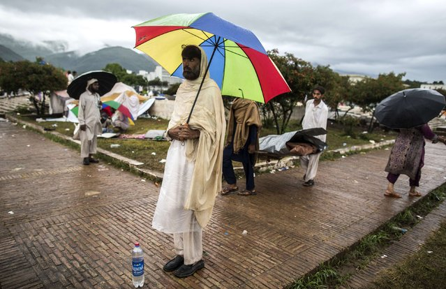 An anti-government protester stands as fellow protesters carry their belongings in the premises of the President and Parliament Houses during the Revolution March in Islamabad September 5, 2014. Pakistan's parliament threw its weight behind embattled Prime Minister Nawaz Sharif on Tuesday as a deepening crisis over violent protests demanding his resignation prompted fears of an army intervention. (Photo by Zohra Bensemra/Reuters)