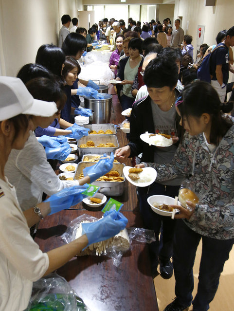 Flood evacuees receive hot meals at the City Hall in Joso, Ibaraki prefecture, north of Tokyo, Thursday, September 10, 2015. Raging floodwaters broke through a flood berm Thursday and swamped the city north of Tokyo, washing away houses, forcing dozens of people to rooftops to await helicopter rescues. (Photo by Shizuo Kambayashi/AP Photo)