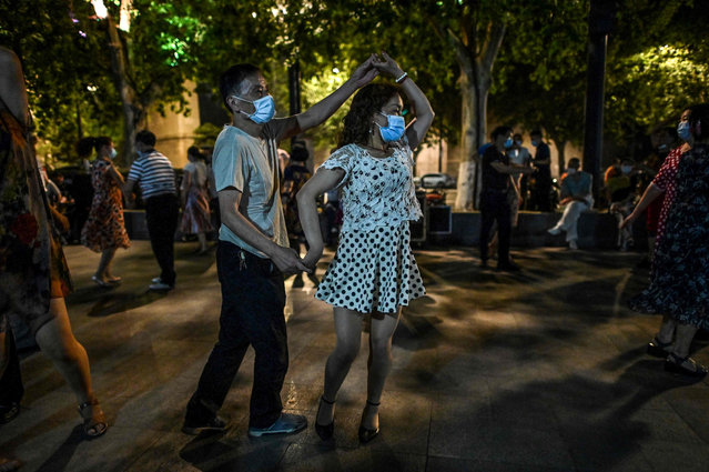 "People wearing facemasks dance in a park next to Yangtze River in Wuhan, China's central Hubei province on May 27, 2020. China's foreign minister on May 24 said the country was ""open"" to international cooperation to identify the source of the disease, but any investigation must be led by the World Health Organization and ""free of political interference"". (Photo by Hector Retamal/AFP Photo)"