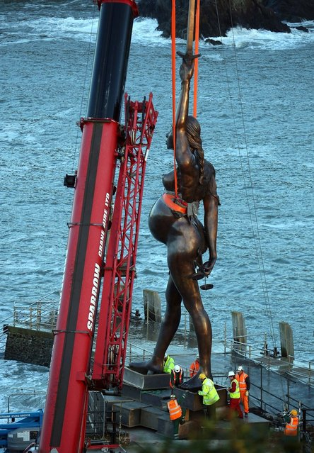Contractors move Damien Hirst's bronze sculpture of a pregnant woman into position on the harbour wall on October 16, 2012 in Ilfracombe, England. The bronze-clad, sword-wielding 65ft (20m) statue, named Verity, has been controversially given to the seaside town by the artist, on a 20-year loan and was erected by crane on the pier.  (Photo by Matt Cardy)