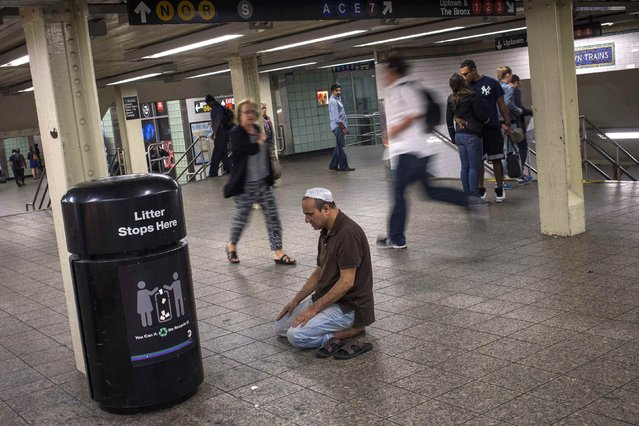 Miganur Rahman, a Bangladeshi Muslim immigrant, performs the night-time Islamic Isha prayer while commuting through the Times Square subway station in Midtown Manhattan, New York September 23, 2014. (Photo by Adrees Latif/Reuters)
