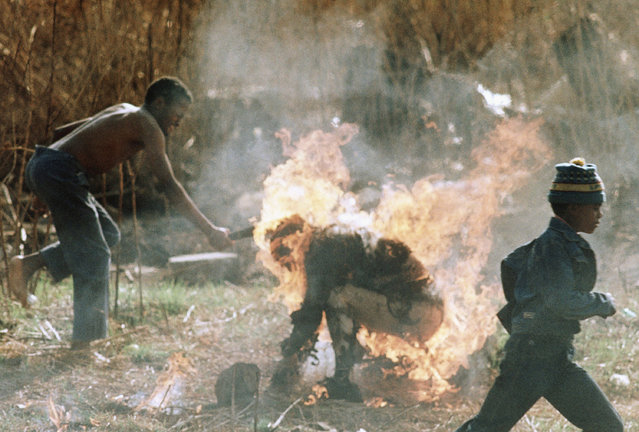 A small boy runs past as a youth clubs the burning body of a man identified as a Zulu Inkatha supporter and set alight by rival African National Congress supporters in Soweto, South Africa, September 15, 1990. (Photo by Seb Balic/AP Photo)