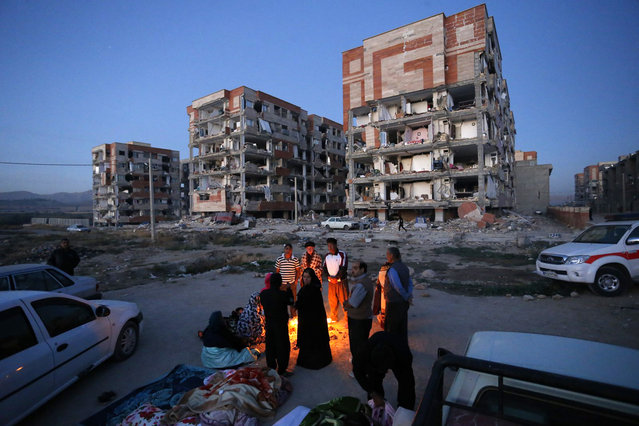 In this photo provided by the Iranian Students News Agency, ISNA, survivors of the earthquake warm themselves in front of destroyed buildings at the city of Sarpol-e-Zahab in western Iran, Monday, November 13, 2017. (Photo by Pouria Pakizeh/ISNA via AP Photo)