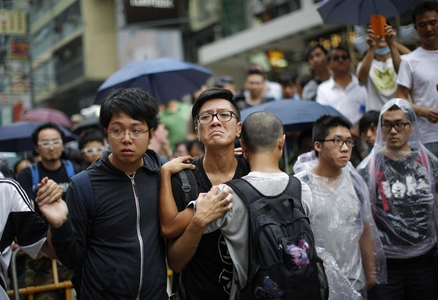 A pro-democracy protester cries after a scuffle with anti-Occupy Central protesters as they try to remove a barricade at a main street at Hong Kong's Mongkok shopping district October 4, 2014. Fresh scuffles broke out on Saturday between Hong Kong pro-democracy protesters and opponents of the week-long demonstrations, reigniting concerns that the Chinese-controlled city's worst unrest in decades could take a violent turn. (Photo by Carlos Barria/Reuters)