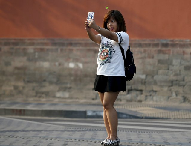 A woman wearing a four-leaf clover-like hairpin takes a selfie nearby Nanluoguxiang street in Beijing, China, September 16, 2015. (Photo by Kim Kyung-Hoon/Reuters)
