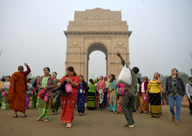 An Indian street vendor selling projectile toys around the India Gate monument tries to attract a group of tourists from Myanmar in New Delhi, India, Tuesday, November 14, 2017. The India Gate is a ceremonial arch that honors the Indian soldiers who died in the First World War. (Photo by R.S. Iyer/AP Photo)