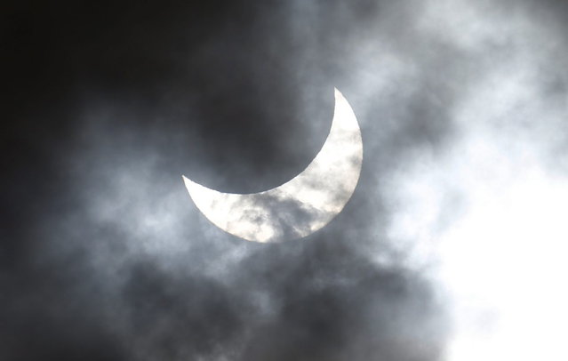Clouds obscure the moon passing in front of the sun as it approaches a full solar eclipse in the northern Australian city of Cairns November 14, 2012. (Photo by Tim Wimborne/Reuters)