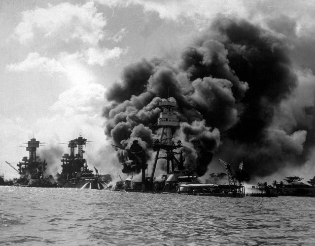 The USS Arizona burning furiously in Pearl Harbour (Pearl Harbor) after the Japanese attack. To the left of her are USS Tennessee and the sunken USS West Virginia. (Photo by Hulton Archive/Getty Images)