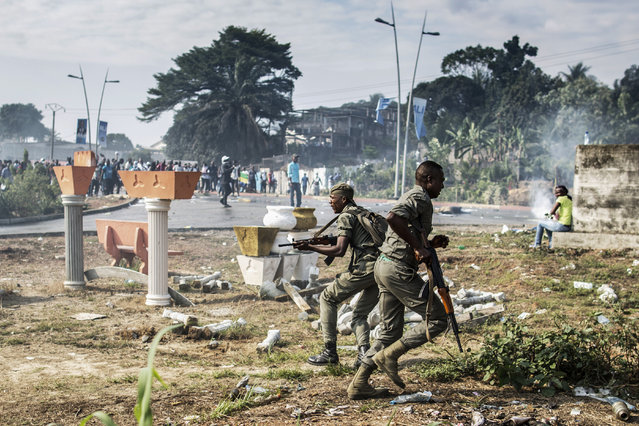 Gabonese soldiers run to take position as supporters of opposition leader Jean Ping protest in front of security forces blocking a demonstration trying to reach the electoral commission in Libreville on August 31, 2016. Bongo won by a narrow 5,594 votes of a total 627,805 registered voters. Turnout was 59.46 percent nationwide but soared to 99.93 percent in one of the country's nine provinces – the Haut-Ogooue, heartland of Bongo's Teke ethnic group – in a result hotly contested by the opposition. (Photo by Marco Longari/AFP Photo)