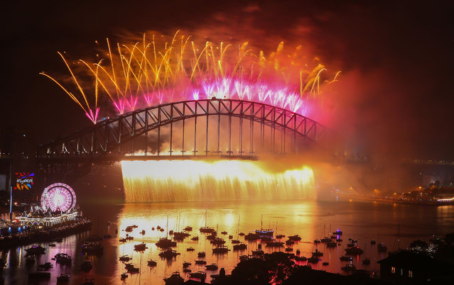 Fireworks explode from the Sydney Harbour Bridge and the Sydney Opera House during the midnight fireworks display on New Year's Eve on New Year's Eve on January 1, 2018 in Sydney, Australia. (Photo by Scott Barbour/City of Sydney/Getty Images)