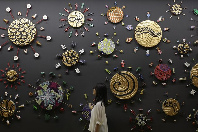 "A person looks at the creation named ""Hong Kong Toy Painting"" by artist Yinka Shonibare MBE (RA)  during the media preview of Art Taipei 2014, October 30, 2014. Art Taipei 2014 will be held from October 31 to November 3 at the Taipei World Trade Centre. (Photo by Pichi Chuang/Reuters)"