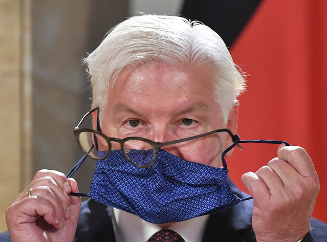 German President Frank-Walter Steinmeier struggles with his glasses and face mask as he attends a press conference after visiting the Salzburg Festival in Salzburg, Austria, Saturday, August 22, 2020. (Photo by Kerstin Joensson/AP Photo)