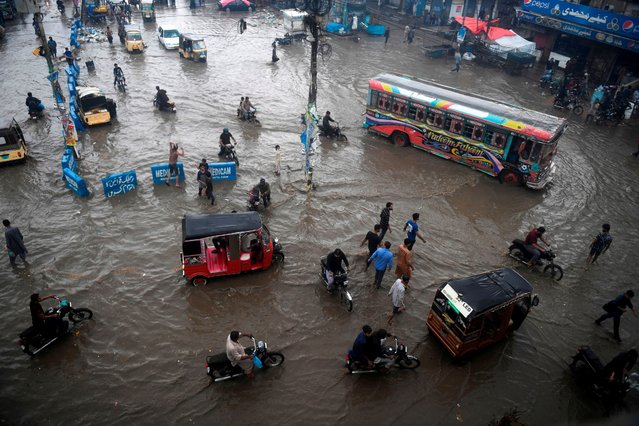 Commuters make their way along a flooded street after heavy monsoon rains in Pakistan's port city of Karachi on August 7, 2020. (Photo by Asif Hassan/AFP Photo)