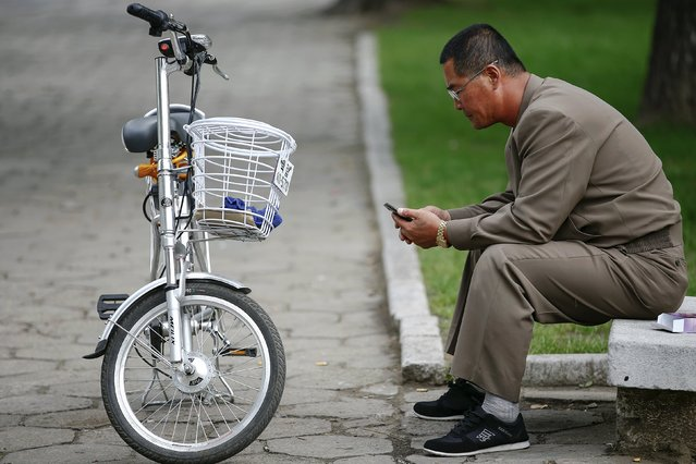 A man uses his mobile phone next to an electric bicycle in downtown Pyongyang, North Korea October 8, 2015. (Photo by Damir Sagolj/Reuters)