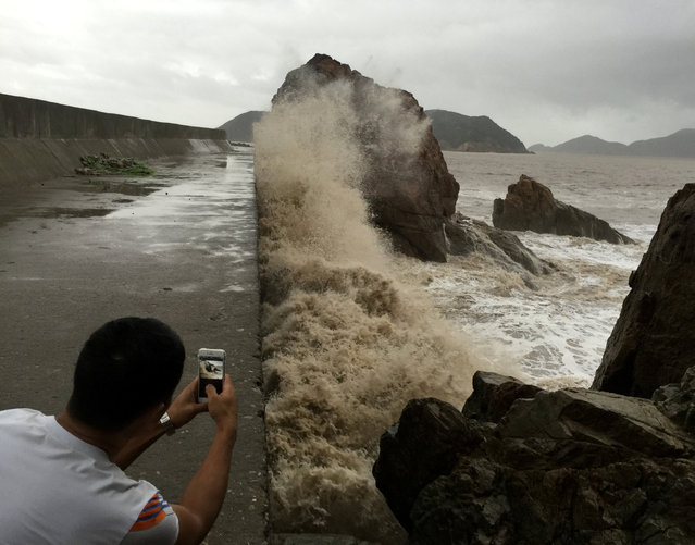 A man records waves whipping the shore before Typhoon Meranti makes a landfall on southeastern China, in Wenling, Zhejiang province, China, September 14, 2016. (Photo by Reuters/Stringer)