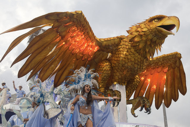 A dancer from the Aguia de Ouro samba school performs on a float during a carnival parade in Sao Paulo, Brazil, Saturday, February 9, 2013. (Photo by Andre Penner/Associated Press)