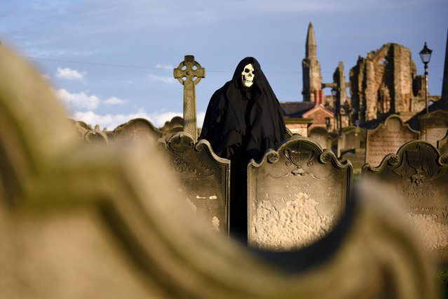 "A man dressed as the Grim Reaper poses for pictures during the biannual ""Whitby Goth Weekend"" (WGW) festival in Whitby, Northern England, on November 2, 2014. (Photo by Oli Scarff/AFP Photo)"