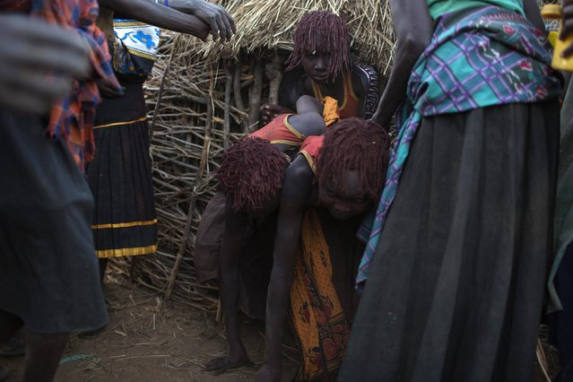 Pokot girls are encouraged to leave their hut and make their way to a place where they will take off their clothes and wash during their circumcision ceremony in a village about 80 kilometres from the town of Marigat in Baringo County, October 16, 2014. (Photo by Siegfried Modola/Reuters)