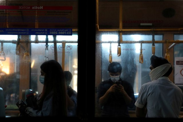 People wearing protective masks travel on a public bus amid the coronavirus disease (COVID-19) outbreak in Kuala Lumpur, Malaysia, June 26, 2020. (Photo by Lim Huey Teng/Reuters)