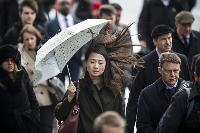 A woman struggles to hold her umbrella during windy weather on London Bridge on October 21, 2014 in London, England. Despite weather warnings issued by the Met Office for high winds and rain off the back of Hurricane Gonzalo, those predictions didn't materialise in London. (Photo by Dan Kitwood/Getty Images)