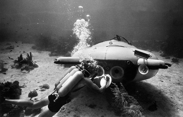 "French explorer and oceanographer Jacques-Yves Cousteau near his ""diving saucer"" during an undersea exploration in the Red Sea, in June of 1963. Together with Jean Mollard, he created the SP-350, a two-man submarine that could reach a depth of 350 m below the ocean's surface. (Photo by OFF/AFP Photo)"