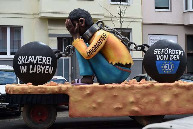 """A carnival float, depicting a migrant with chains with the writings """"Slavery in Libya"""" and """"supported by the EU"""", is pictured during a carnival parade on Rose Monday on February 12, 2018 in Duesseldorf, western Germany. (Photo by Patrik Stollarz/Getty Images)"""