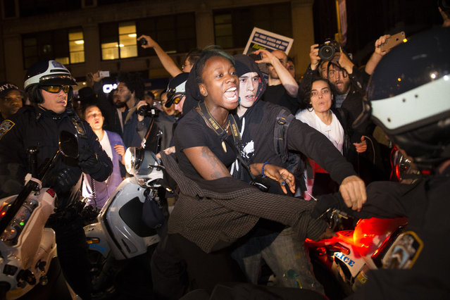 A protestor scuffles with police during a march towards Times Square after the announcement of the grand jury decision not to indict police officer Darren Wilson in the fatal shooting of Michael Brown, an unarmed black 18-year-old, Monday, November 24, 2014, in New York. (Photo by John Minchillo/AP Photo)