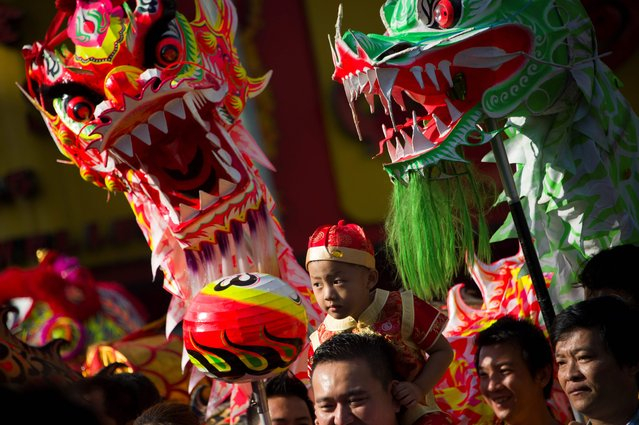 Members of a dragon dance troupe take part in celebrations marking the first day of the Lunar New Year in Yangon's Chinatown district on February 16, 2018. The 2018 Lunar New Year fell on February 16 across much of Asia, marking the start of the Year of the Dog. (Photo by Ye Aung Thu/AFP Photo)