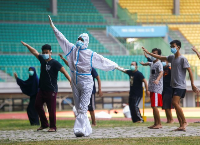A health worker wearing protective suit and patients exercise at the Patriot Chandrabhaga Stadium which has been converted into a quarantine house amid the coronavirus disease (COVID-19) outbreak, in Bekasi, on the outskirts of Jakarta, Indonesia, September 28, 2020. (Photo by Ajeng Dinar Ulfiana/Reuters)