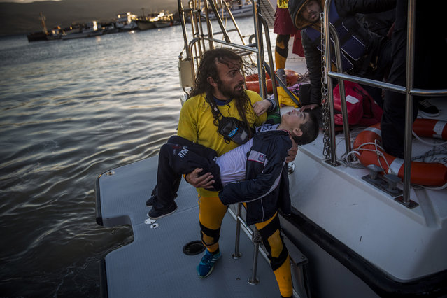 A volunteer carries a young boy after a boat with refugees and migrants sank while crossing the Aegean sea from Turkey to the Greek island of Lesbos, on Wednesday, October 28, 2015. The condition of the child is not known. The Greek coast guard said it rescued 242 refugees or economic migrants off the eastern island of Lesbos Wednesday after the wooden boat they traveled in capsized, leaving at least three dead on a day when another 8 people drowned trying to reach Greece. (Photo by Santi Palacios/AP Photo)