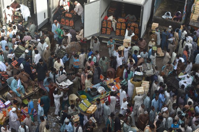 Traders and buyers gather at a fruit market in Lahore on September 27, 2020. (Photo by Arif Ali/AFP Photo)