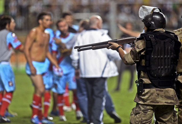 A Brazilian police officer aims his shotgun loaded with pellets at Argentina's Arsenal soccer players at the end of the Copa Libertadores soccer match against Brazil's Atletico Mineiro in Belo Horizonte, Brazil, on April 3, 2013. Authorities said the players will likely be charged after throwing punches and kicking the officers who were trying to protect the referees .Atletico Mineiro won 5–2. (Photo by Eugenio Savio/Associated Press)
