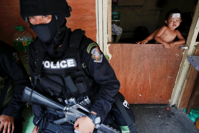 A baby looks at an armed member of a police SWAT team during a drug raid, in Manila, Philippines, October 7, 2016. (Photo by Damir Sagolj/Reuters)