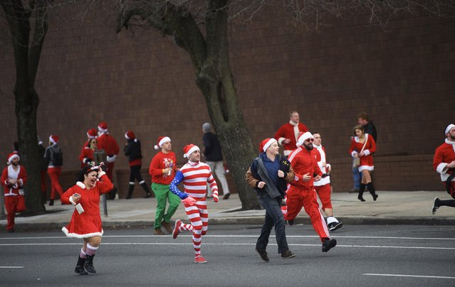 "People in Santa Claus outfits participate in the ""Running of the Santas"" in Philadelphia, Pennsylvania December 13, 2014. (Photo by Mark Makela/Reuters)"