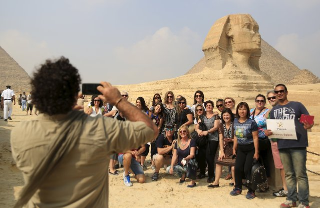 Tourists take a souvenir photo in front of the Sphinx at the Giza Pyramids on the outskirts of Cairo, Egypt, November 8, 2015. Egypt's Tourism Minister Hesham Zaazou said Cairo regretted the suspension of flights and was doing all it could to secure its airports and tourist sites, adding that he would fly to Sharm al-Sheikh to oversee measures to support tourists there. (Photo by Amr Abdallah Dalsh/Reuters)