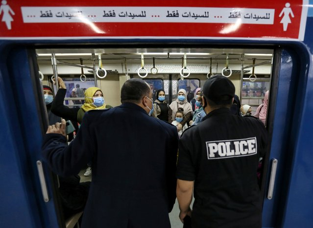 """Police members check on passengers wearing protective face mask inside the underground Al Shohadaa """"Martyrs"""" metro while Egypt ramps up its efforts to slow down the spread of the coronavirus disease (COVID-19) in Cairo, Egypt on November 21, 2020. (Photo by Mohamed Abd El Ghany/Reuters)"""