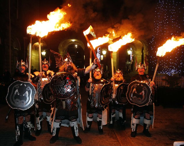 Up Helly Aa vikings from the Shetland Islands hold lit torches during the annual torchlight procession to mark the start of Hogmanay (New Year) celebrations in Edinburgh, Scotland December 30, 2014. The annual torchlight procession finishes with a fireworks display at Calton Hill in Edinburgh. (Photo by Russell Cheyne/Reuters)