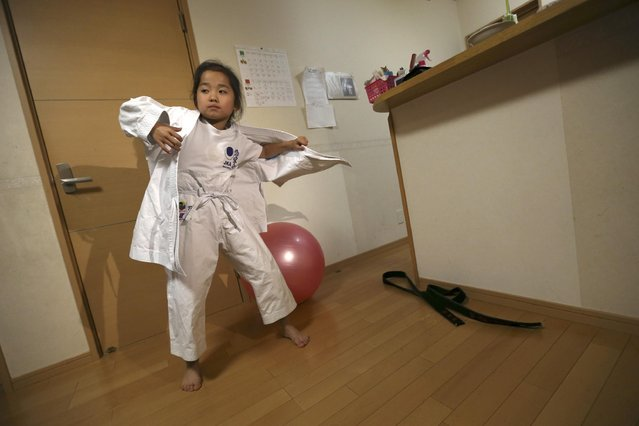 In this November 18, 2015 photo, 9-year-old Mahiro Takano, center, three-time Japan karate champion in her age group wears a karate outfit at home before going to her karate practice in Nagaoka, Niigata Prefecture, north of Tokyo. (Photo by Eugene Hoshiko/AP Photo)