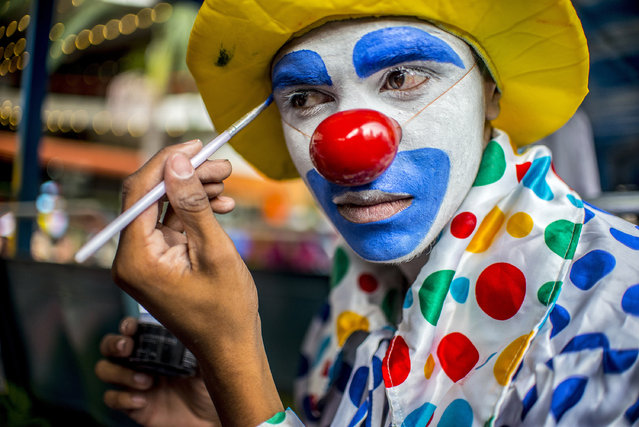 A clown adjusts his makeup before a protest by a group of clowns in the old center of Sao Paulo, Brazil on October 24, 2016. (Photo by Cris Faga via ZUMA Wire)