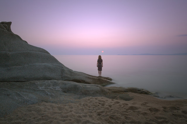 Woman standing on an edge of the shore and watching the sunrise by rocks with strange shape. Long exposure shot in Aegean Sea, Greece. (Photo by Getty Images/iStockphoto)
