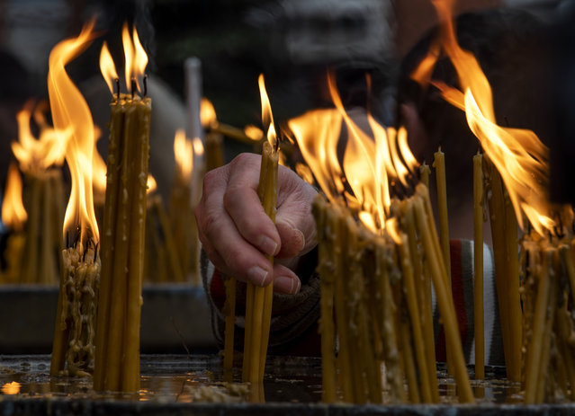 An Orthodox believer lights candles during a Christmas mass outside the central Orthodox Church of Saint Clement in Skopje, Republic of North Macedonia, 07 January 2021. Orthodox Christians celebrate Christmas Day on 07 January according to the Julian calendar. (Photo by Georgi Licovski/EPA/EFE)