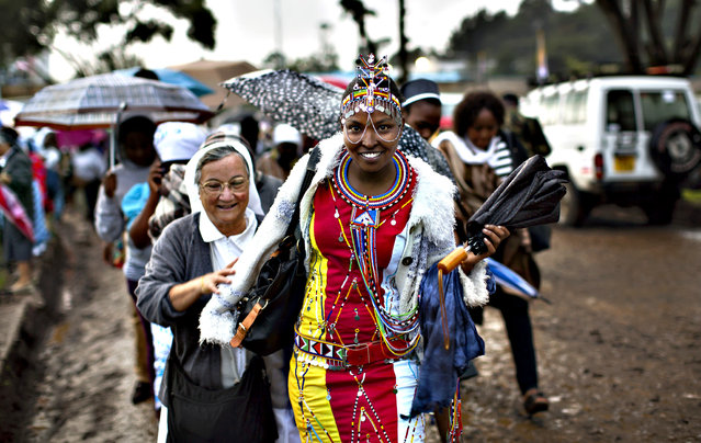 A Catholic sister and a Maasai woman arrive just after dawn in the rain and mud to attend a Mass to be given by Pope Francis at the campus of the University of Nairobi in Kenya Thursday, November 26, 2015. Pope Francis is in Kenya on his first-ever trip to Africa, a six-day pilgrimage that will also take him to Uganda and the Central African Republic. (Photo by Ben Curtis/AP Photo)