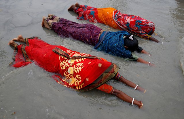 """Women worship to Hindu sun god as they take a dip at the confluence of the river Ganges and the Bay of Bengal on the occasion of """"Makar Sankranti"""" festival at the Sagar Island, amidst the spread of the coronavirus disease (COVID-19), in the eastern state of West Bengal, India, January 14, 2021. (Photo by Rupak De Chowdhuri/Reuters)"""