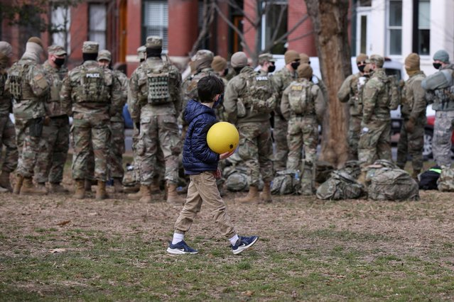 A boy walks past members of the National Guard after playing at Lincoln Park in Washington, U.S., January 18, 2021. (Photo by Caitlin Ochs/Reuters)