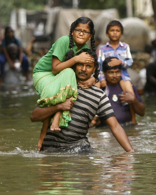 People carry children on their shoulders and wade through flood waters in Chennai, India, Thursday, December 3, 2015. (Photo by AP Photo)