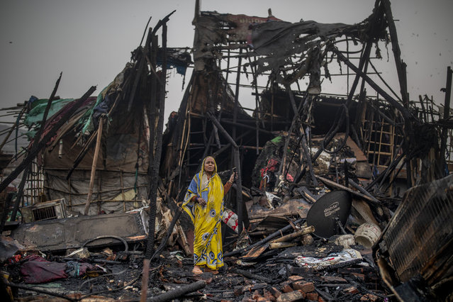 A woman stands on the debris of a fire at a slum area in New Delhi, India, Saturday, January 23, 2021. More than 50 huts of a slum inhabited mostly by ragpickers were gutted in a fire that broke out Saturday afternoon. There were no casualties. (Photo by Altaf Qadri/AP Photo)