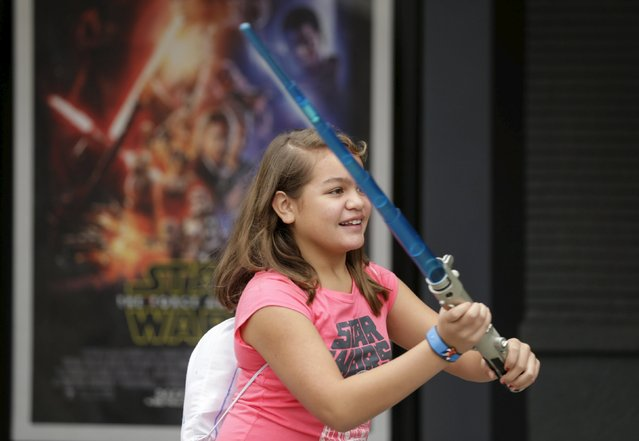 A child plays with a light saber outside the Star Wars Launch Bay grand opening at Disney's Hollywood Studios in Orlando, Florida December 4, 2015. (Photo by Scott Audette/Reuters)