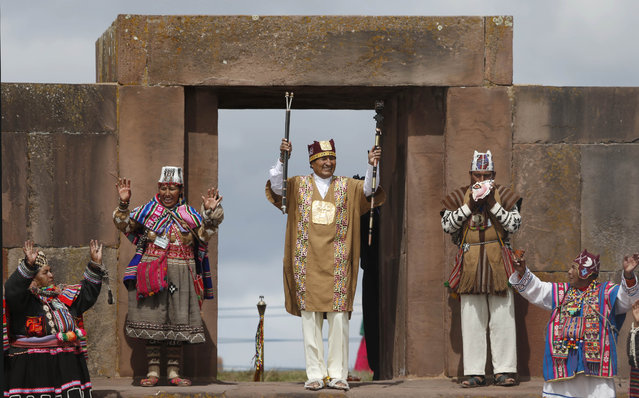 Bolivia's president Evo Morales holds his scared staffs of power during a blessing by Aymaran spiritual guides, in a traditional ceremony at the archeological site Tiwanaku, Bolivia, Wednesday, January 21, 2015. Morales is set to begin a new term Thursday, that will make him the Andean nation's longest-serving leader, riding high on a wave of unprecedented growth and stability. (Photo by Juan Karita/AP Photo)