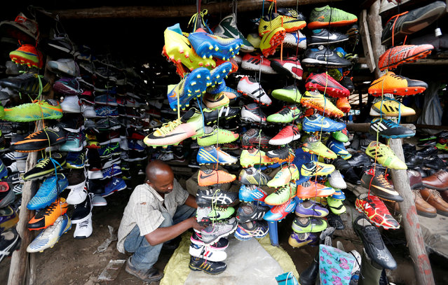 A trader arranges second-hand pairs of soccer shoes for sale at an open air market in Nairobi, Kenya May 18, 2018. (Photo by Thomas Mukoya/Reuters)