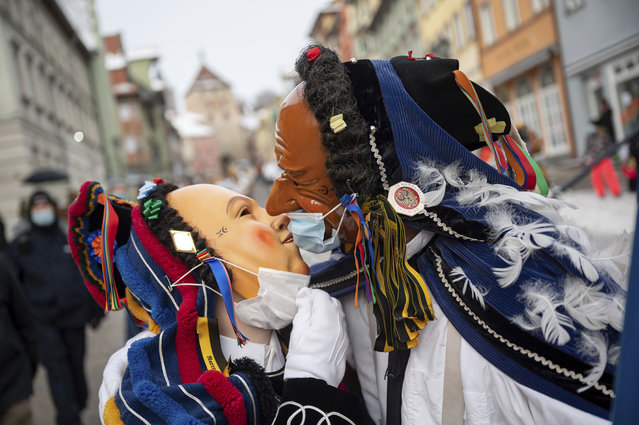 """Two fools with surgical masks over their faces celebrate on Shrove Monday in the city center of Rottweil, Germany, Monday, February 15, 2021. Due to the coronavirus pandemic, the fool's jump, a traditional part of the city's carnival celebrations, was officially cancelled, but some fools were still on the move. The Rottweiler """"Narrensprung"""" is one of the highlights of the Swabian-Alemannic carnival in the southwest German region. (Photo by Sebastian Gollnow/dpa via AP Photo)"""